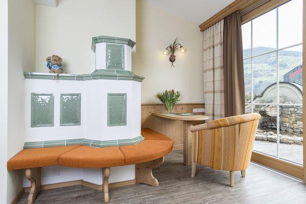 gemütliche Sitzecke mit Kachelofen in der Juniorsuite Tirol deluxe